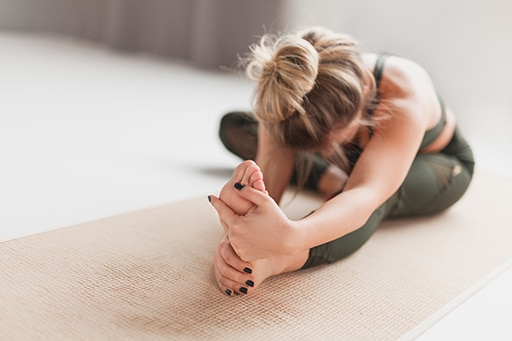 Unrecognizable female in sportswear performing Head to Knee Forward Bend while sitting on floor at home